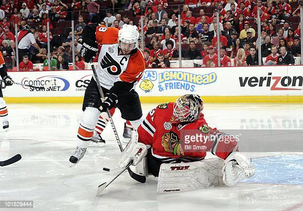 Chicago Blackhawks goalie Antti Niemi gets in position to stop the puck as Mike Richards of the Philadelphia Flyers stands behind at Game One of the...