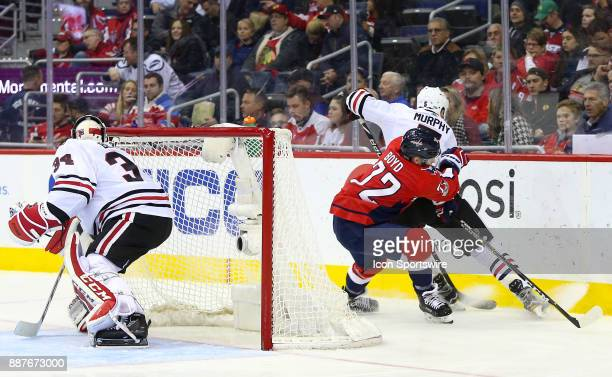Chicago Blackhawks goalie JF Berube watches a check by Washington Capitals center Travis Boyd on defenseman Connor Murphy during a NHL game between...