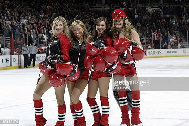 Chicago Blackhawks ice crew girls pose with some of the Blackhawk hard hats during a game against the Pittsburgh Penguins on February 27 2009 at the...