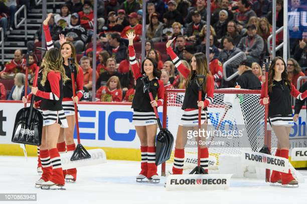 Chicago Blackhawks Ice Crew members wave to fans during an NHL hockey game between the Montreal Canadiens and the Chicago Blackhawks on December 09...