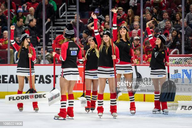 Chicago Blackhawks Ice Crew members wave to fans during an NHL hockey game between the Vancouver Canucks and the Chicago Blackhawks on February 07 at...
