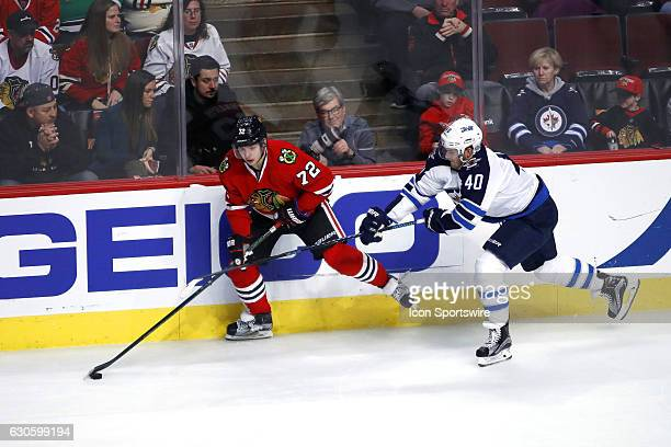 Chicago Blackhawks Left Wing Artemi Panarin battles with Winnipeg Jets Right Wing Joel Armia to handle a loose puck during the third period of a game...