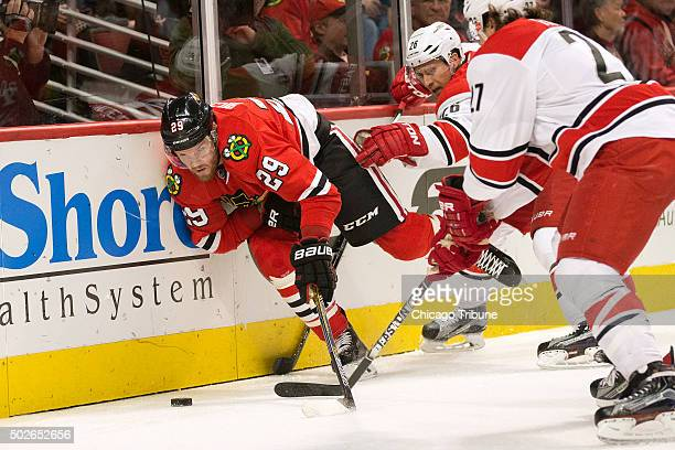 Chicago Blackhawks left wing Bryan Bickell falls into the boards as he chases the puck during the first period on Sunday Dec 27 at the United Center...