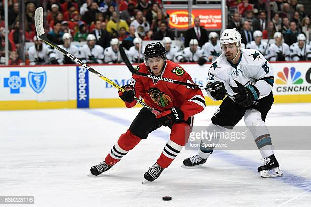 Chicago Blackhawks left wing Vinnie Hinostroza and San Jose Sharks right wing Joonas Donskoi fight for the puck in the first period during a game...