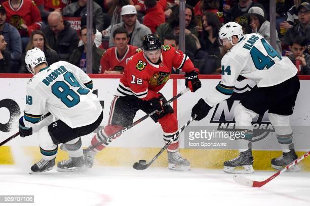 Chicago Blackhawks right wing Alex DeBrincat battles for the puck with San Jose Sharks left wing Mikkel Boedker and San Jose Sharks defenseman...