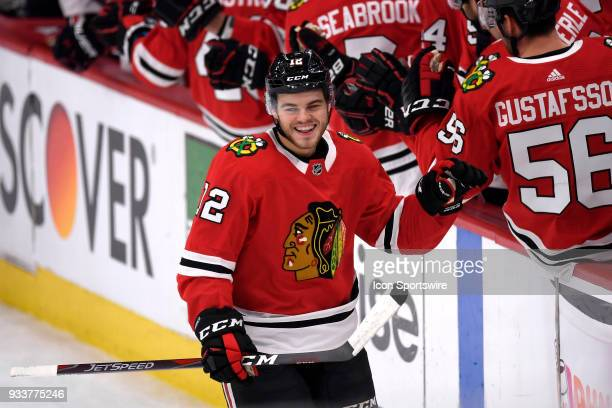 Chicago Blackhawks right wing Alex DeBrincat celebrates with teammates after scoring a goal in the first period of play during a game between the...