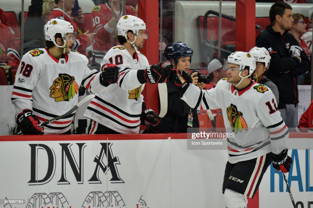 Chicago Blackhawks Right Wing Alex DeBrincat (12) is congratulated by his bench after scoring a goal in the third period during a game between the Carolina Hurricanes and the Chicago Blackhawks at the PNC Arena on Raleigh, NC on November 11, 2017. Chicago defeated Carolina 4-3 in overtime.