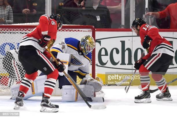 Chicago Blackhawks right wing Alex DeBrincat pokes the puck past St Louis Blues goaltender Jake Allen for a goal as Chicago Blackhawks center Artem...