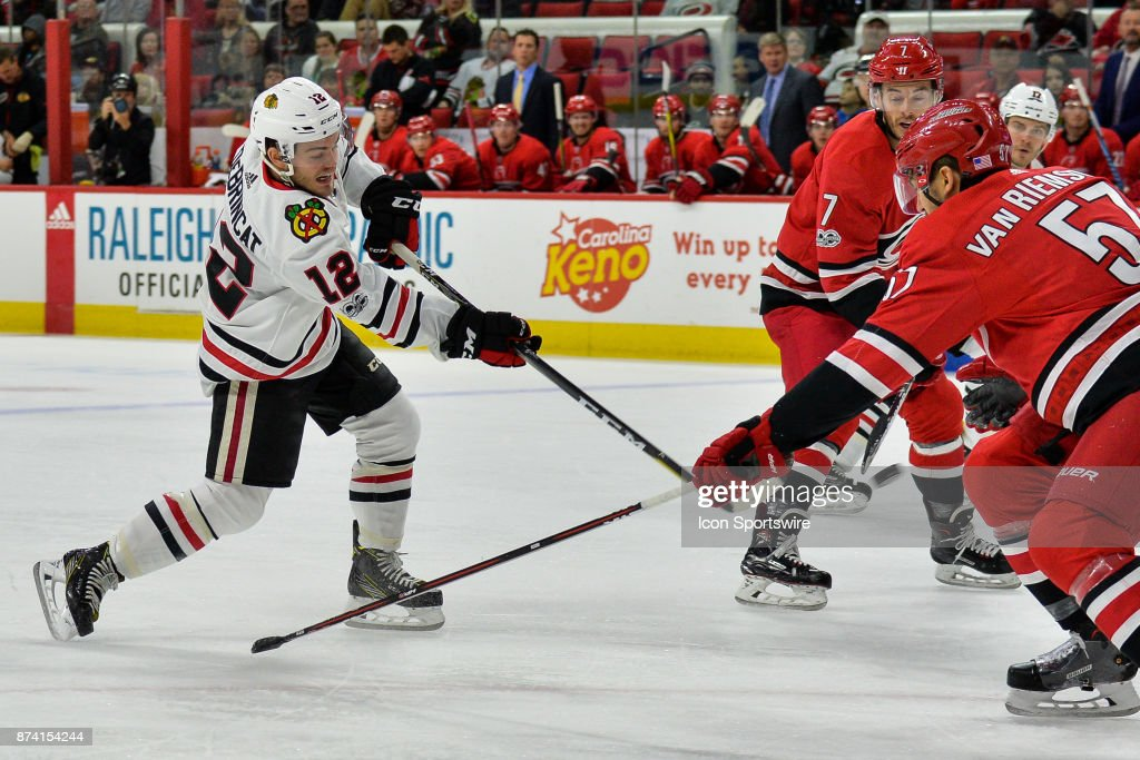 Chicago Blackhawks Right Wing Alex DeBrincat (12) takes a shot on net during a game between the Carolina Hurricanes and the Chicago Blackhawks at the PNC Arena on Raleigh, NC on November 11, 2017. Chicago defeated Carolina 4-3 in overtime.