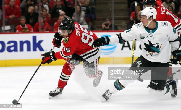 Chicago Blackhawks right wing Dylan Sikura and San Jose Sharks defenseman Justin Braun chase a puck leading to a Chicago Blackhawks goal in the first...