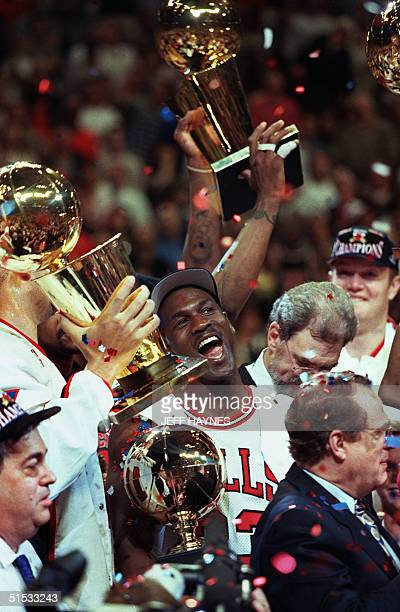 Chicago Bull player Michael Jordan is surrounded by NBA Championship trophies after his team defeated 13 June 1997 the Utah Jazz 9086 to win the 1997...