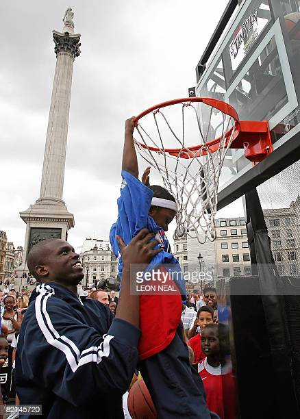 Chicago Bulls basketball player Luol Deng lifts seven year old Shekeem O'Connor up to the hoop during an NBA JamVan press event in Trafalgar Square...