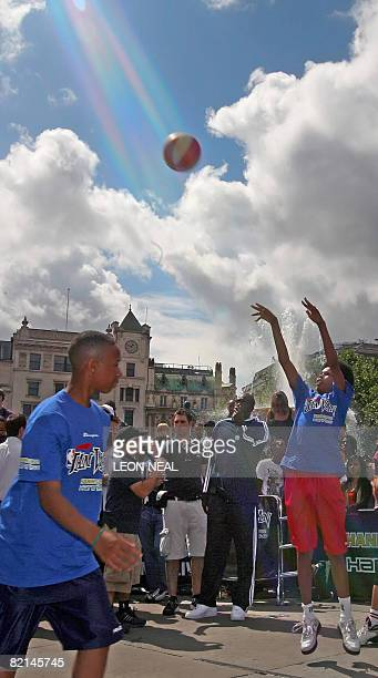 Chicago Bulls basketball player Luol Deng watches as young players throw the ball during an NBA JamVan press event in Trafalgar Square in London on...