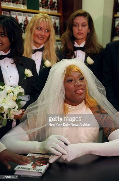 """Chicago Bulls' basketball star Dennis Rodman, dressed in a wedding gown, signs copies of his new book """"Bad As I Wanna Be"""" at Barnes and Noble on..."""