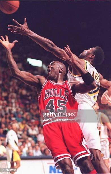 Chicago Bulls basketball star Michael Jordan makes a rebound against Indiana Pacers forward Antonio Davis in the first half 19 March at Market Square...