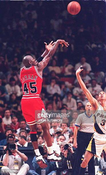 Chicago Bulls basketball star Michael Jordan takes one of his first shots as Indiana Pacers forward Reggie Miller watches in the first half 19 March...