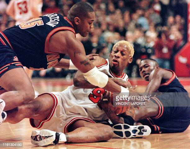 Chicago Bulls forward Dennis Rodman scrambles for the ball with Denver Nuggets forward Danny Forston and guard Anthony Goldwire during the first...