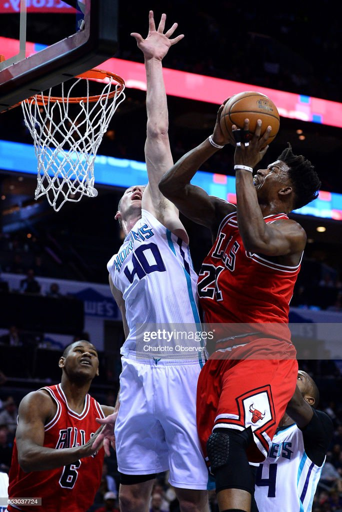 Chicago Bulls forward Jimmy Butler, right, drives hard to the basket for a shot attempt against Charlotte Hornets center Cody Zeller, center, who applies defensive pressure during first half action on Monday, March 13, 2017 at the Spectrum Center in Charlotte, N.C.
