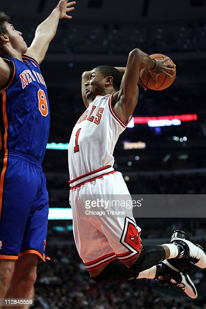 Chicago Bulls guard Derrick Rose flies by New York Knicks forward Danilo Gallinari en route to a dunk in the first quarter at the United Center in...