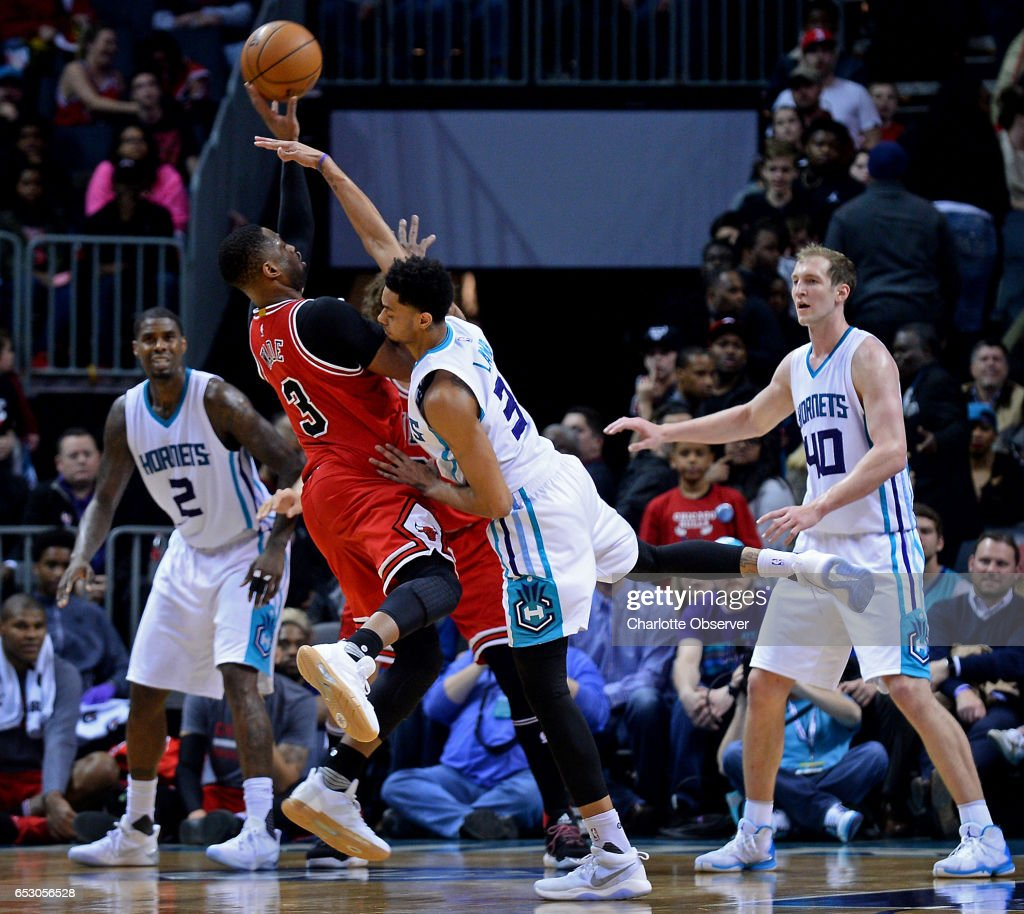 Chicago Bulls guard Dwyane Wade, left, is fouled by Charlotte Hornets guard Jeremy Lamb, right, during late second half action on Monday, March 13, 2017 at the Spectrum Center in Charlotte, N.C. The Bulls defeated the Hornets 115-109.