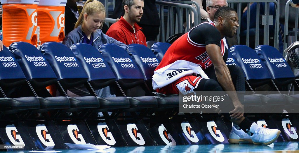 Chicago Bulls guard Dwyane Wade rubs his right leg after being injured on a scramble for the ball during second half action against the Charlotte Hornets on Monday, March 13, 2017 at the Spectrum Center in Charlotte, N.C. Wade would return to action. The Bulls defeated the Hornets 115-109.