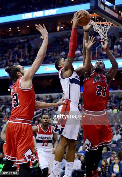 Chicago Bulls guard Jimmy Butler and Bulls center Joakim Noah defend a shot by Washington Wizards guard Bradley Beal in the third quarter at the...