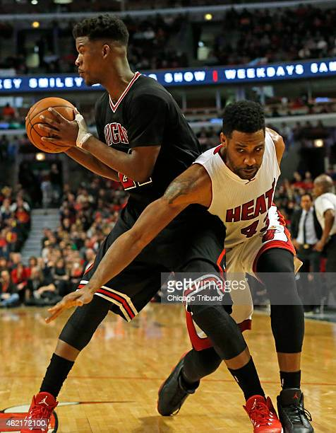 Chicago Bulls guard Jimmy Butler grabs a rebound in front of Miami Heat forward Shawne Williams during the fourth quarter on Sunday Jan 25 at the...