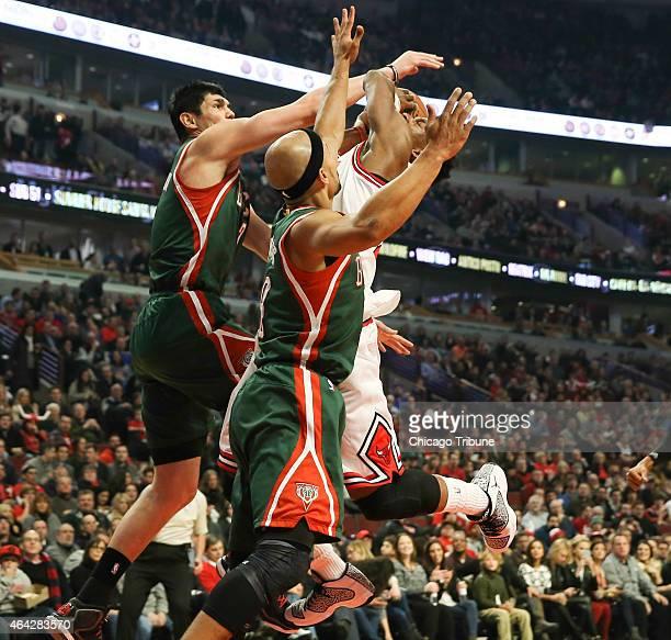 Chicago Bulls guard Jimmy Butler is stopped under the basket by Milwaukee Bucks forward Ersan Ilyasova and Milwaukee Bucks guard Jerryd Bayless...