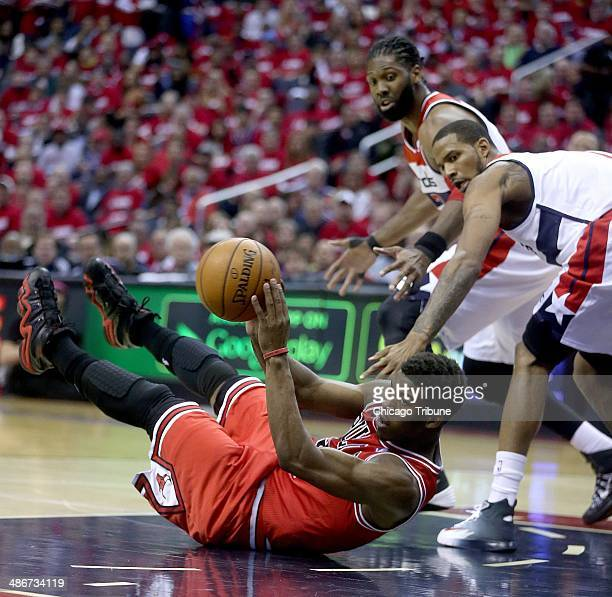 Chicago Bulls guard Jimmy Butler looks to pass the all ball after falling to the floor while being guarded by Washington Wizards forward Trevor Ariza...