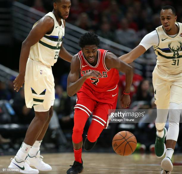 Chicago Bulls guard Justin Holiday chases a loose ball ahead of Milwaukee Bucks forward Khris Middleton and John Henson in the first half on Sunday,...