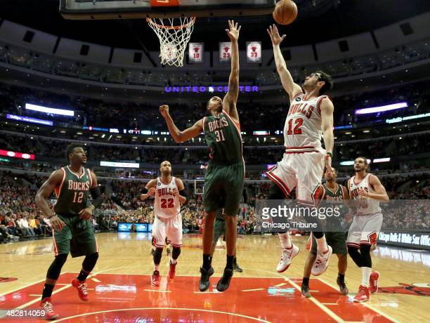 Chicago Bulls guard Kirk Hinrich tries to score on a layup against Milwaukee Bucks center John Henson in the first half at the United Center in...