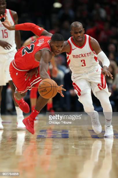 Chicago Bulls guard Kris Dunn and Houston Rockets guard Chris Paul battle for control of a loose ball as the Bulls rally during the second quarter of...
