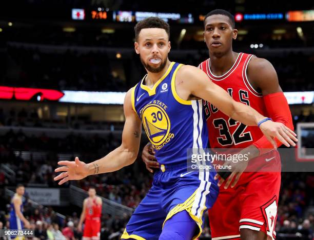 Chicago Bulls guard Kris Dunn defends against Golden State Warriors guard Stephen Curry during the first half at the United Center in Chicago on...