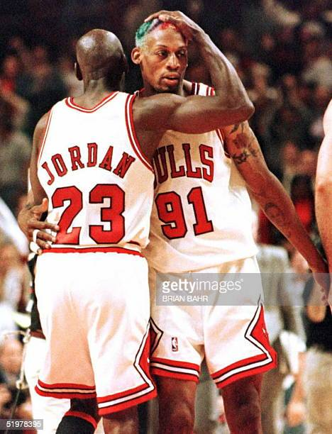 Chicago Bulls guard Michael Jordan congratulates teammate Dennis Rodman 7 June at the end of the third quarter of game two of the NBA Finals at the...