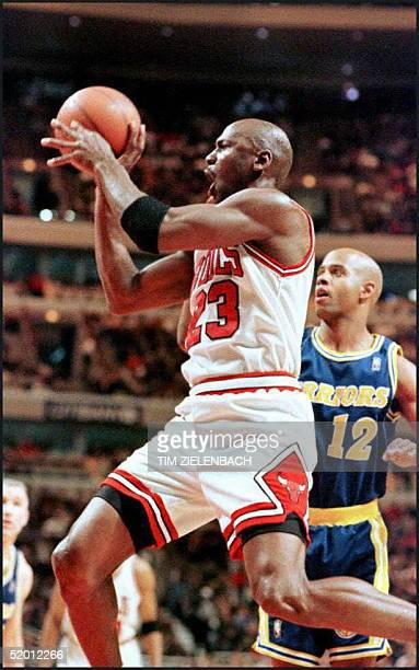 Chicago Bulls guard Michael Jordan drives past Golden State Warriors guard Bimbo Coles in the first quarter 22 February at the United Center in...