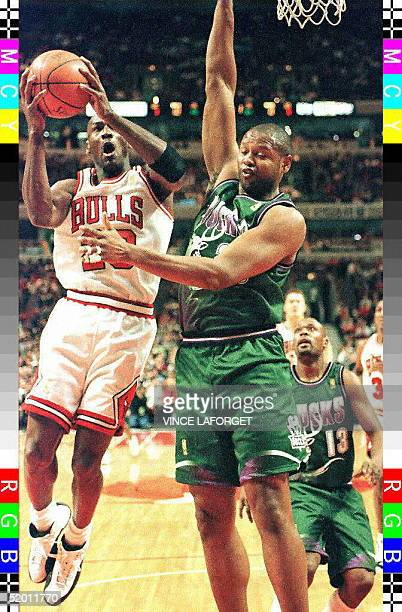 Chicago Bulls guard Michael Jordan drives past Milwaukee Bucks center Andrew Lang as Bucks forward Glenn Robinson looks on in the first quarter 17...