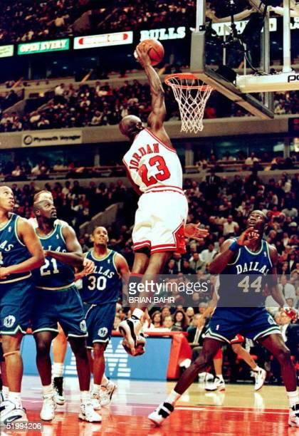 Chicago Bulls guard Michael Jordan dunks the ball as Dallas Mavericks players Lorenzo Williams Lucious Harris George McCloud and Popeye Jones watch...
