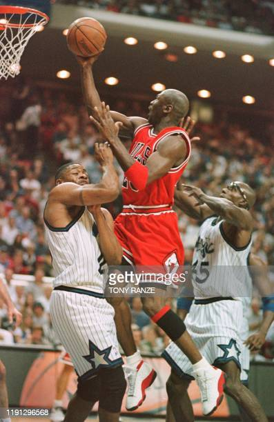 Chicago Bulls guard Michael Jordan goes between Orlando Magic guard Nick Anderson and forward Charles Outlaw for two points during the first period...