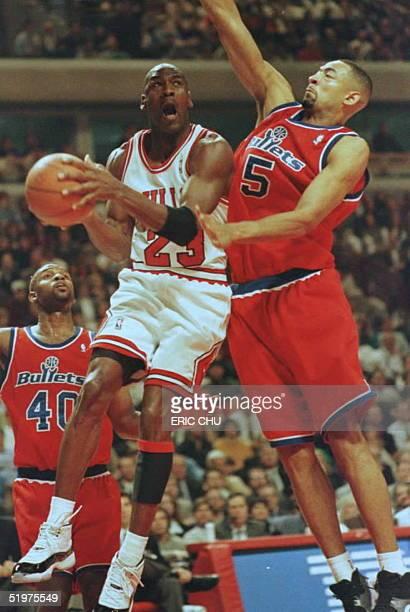 Chicago Bulls guard Michael Jordan goes up for a basket against Washington Bullets forward Juwan Howard 13 March during the first quarter against the...