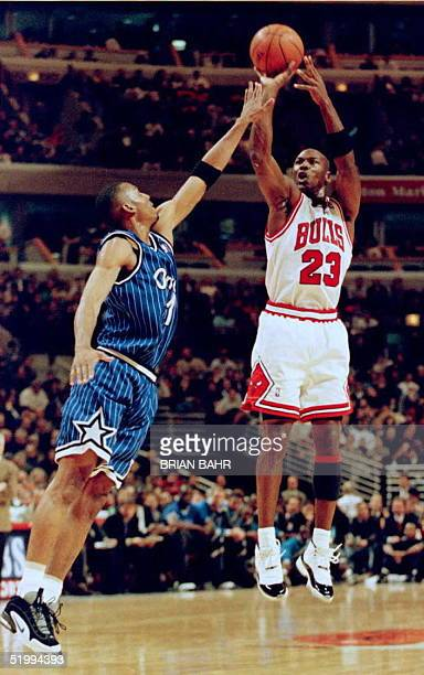 Chicago Bulls guard Michael Jordan shoots a jump shot over Orlando Magic guard Anfernee Hardaway 13 December during the first period at the United...