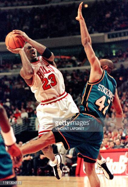 Chicago Bulls guard Michael Jordan shoots around Detroit Pistons guard Jerry Stackhouse during the fourth quarter 15 February at the United Center in...