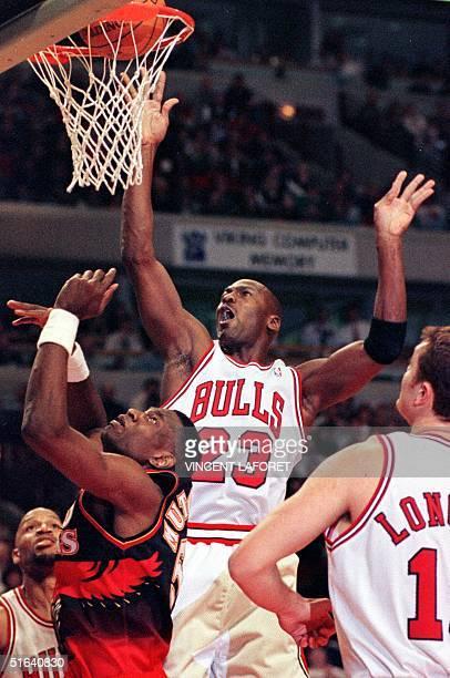 Chicago Bulls guard Michael Jordan tips the ball into the basket over Atlanta Hawks center Dikembe Mutombo as Chicago Bulls center Luc Longley looks...