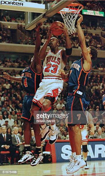 Chicago Bulls' guard Michael Jordan winds his way under the net only to be fouled by New York Knicks' forwards Anthony Mason and JR Reid in the first...