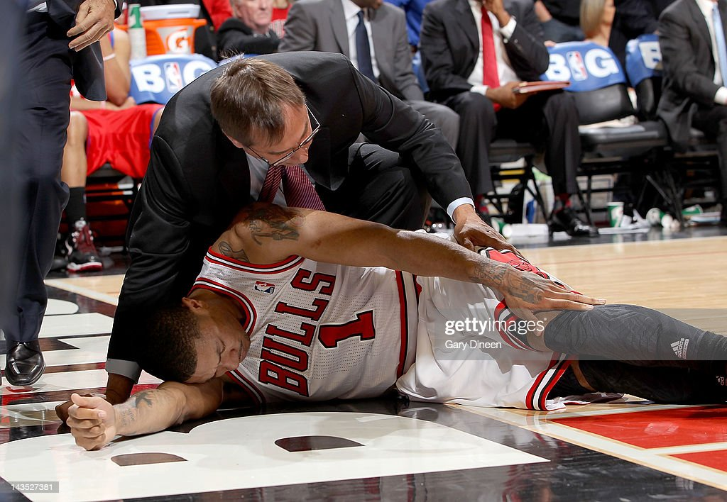 Chicago Bulls Head Athletic Trainer Fred Tedeschi assists Derrick Rose #1 after injuring his knee against the Philadelphia 76ers in Game One of the Eastern Conference Quarterfinals during the 2012 NBA Playoffs on April 28, 2012 at the United Center in Chicago, Illinois.