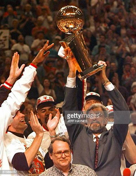 Chicago Bulls head coach Phil Jackson holds the Larry O'Brian trophy after his team beat the Seattle SuperSonics in game six of the NBA Finals at the...