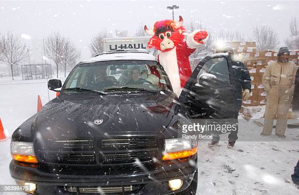 Chicago Bulls mascot Benny The Bull leads a vehicle to the Chicago Bulls food and toy distribution event in the parking lot of the United Center on...