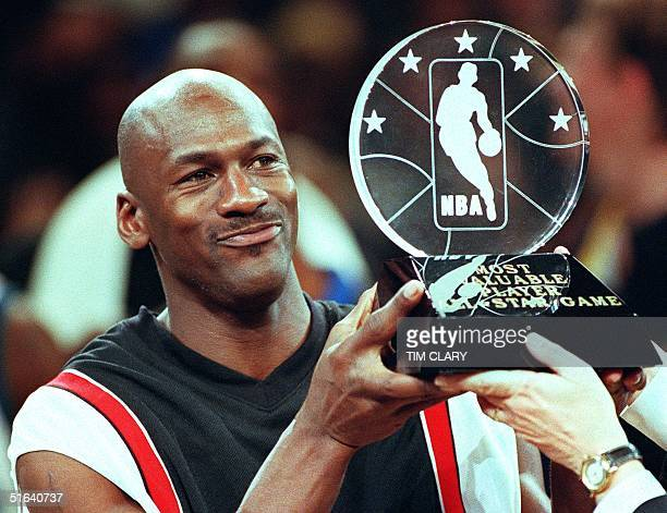 Chicago Bulls' Michael Jordan holds up the Most Valuable Player trophy which he earned in leading the Eastern Conference to victory in the NBA...