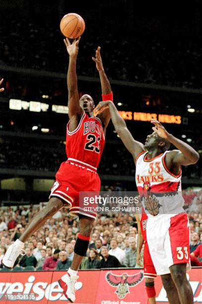 Chicago Bulls Michael Jordan takes a shoot while being guarded by Atlanta Hawks Tyrone Corbin 27 March in Atlanta Ga An NBA attendance record was...