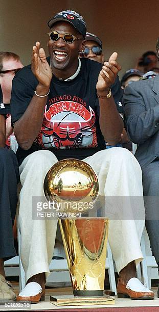 Chicago Bulls player Michael Jordan applauds as he sits with one of the team's six NBA championship trophies he has helped the Bulls win in the past...