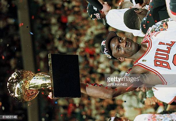 Chicago Bulls player Michael Jordan holds the Larry O'Brien Trophy after his team defeated the Utah Jazz 9086 to win the 1997 NBA Finals at the...